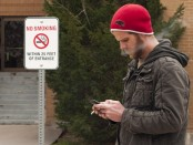 A student smoking a cigarette and texting in front of an entrance to the TB building. Right behind him is a sign that says no smoking within 25 feet of the entrance.