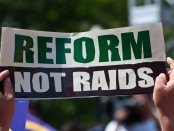 """Reform not raids"" protest sign"