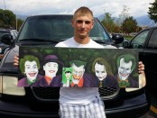 Chris Christman holding his painting depicting the various versions of The Joker.