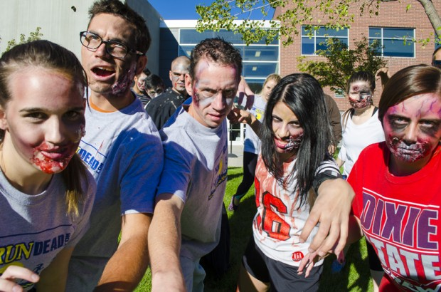 A group of zombies in full make-up walk toward the camera.