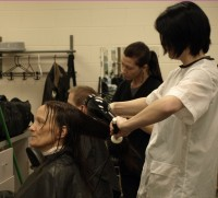 Cindy Fletcher sits for a haircut by student styilst Stacy Bleggi