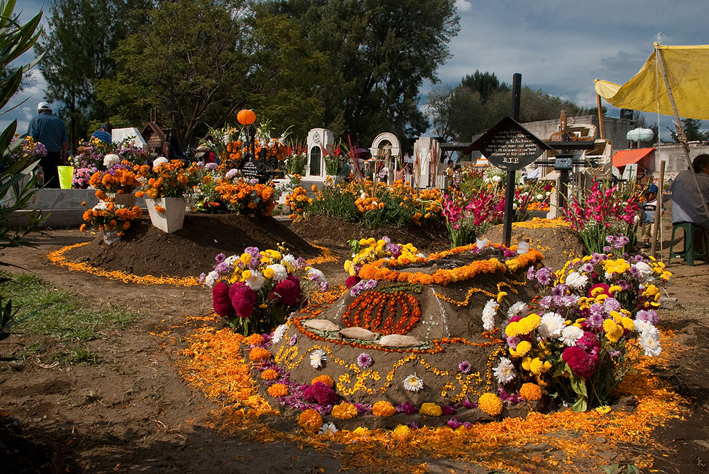 an image of a decorated grave site during day of the dead celebrations at the cemetery