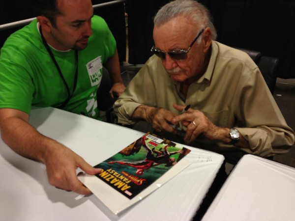 Stan Lee signing a spider-man comic book.