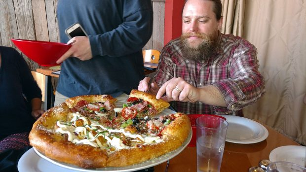 Daniel Poole grabs slice of pizza