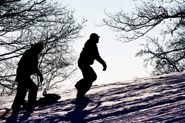 Tobogganers walking uphill
