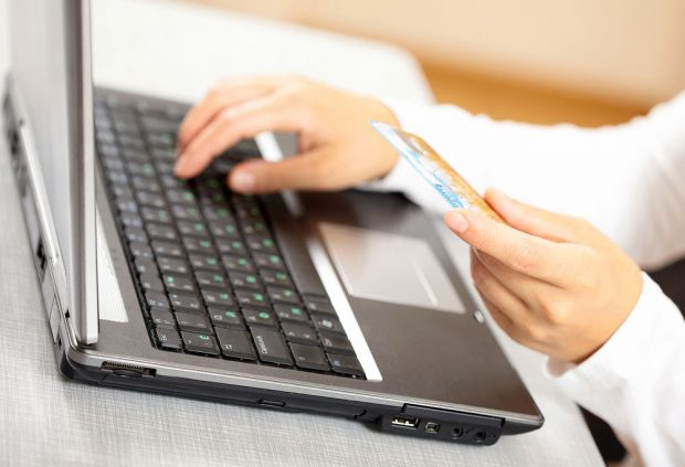 Hands holding credit card and laptop