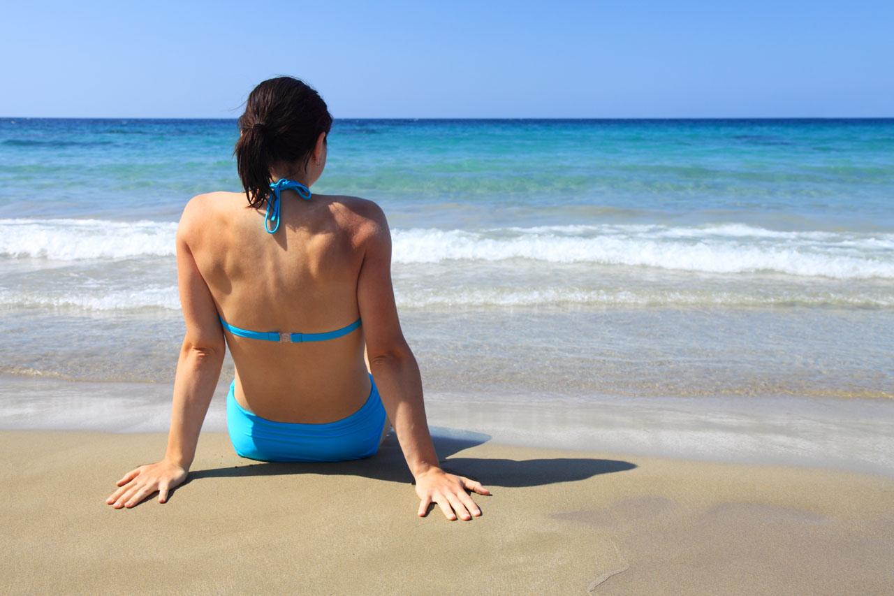 Woman sitting on the beach near the ocean