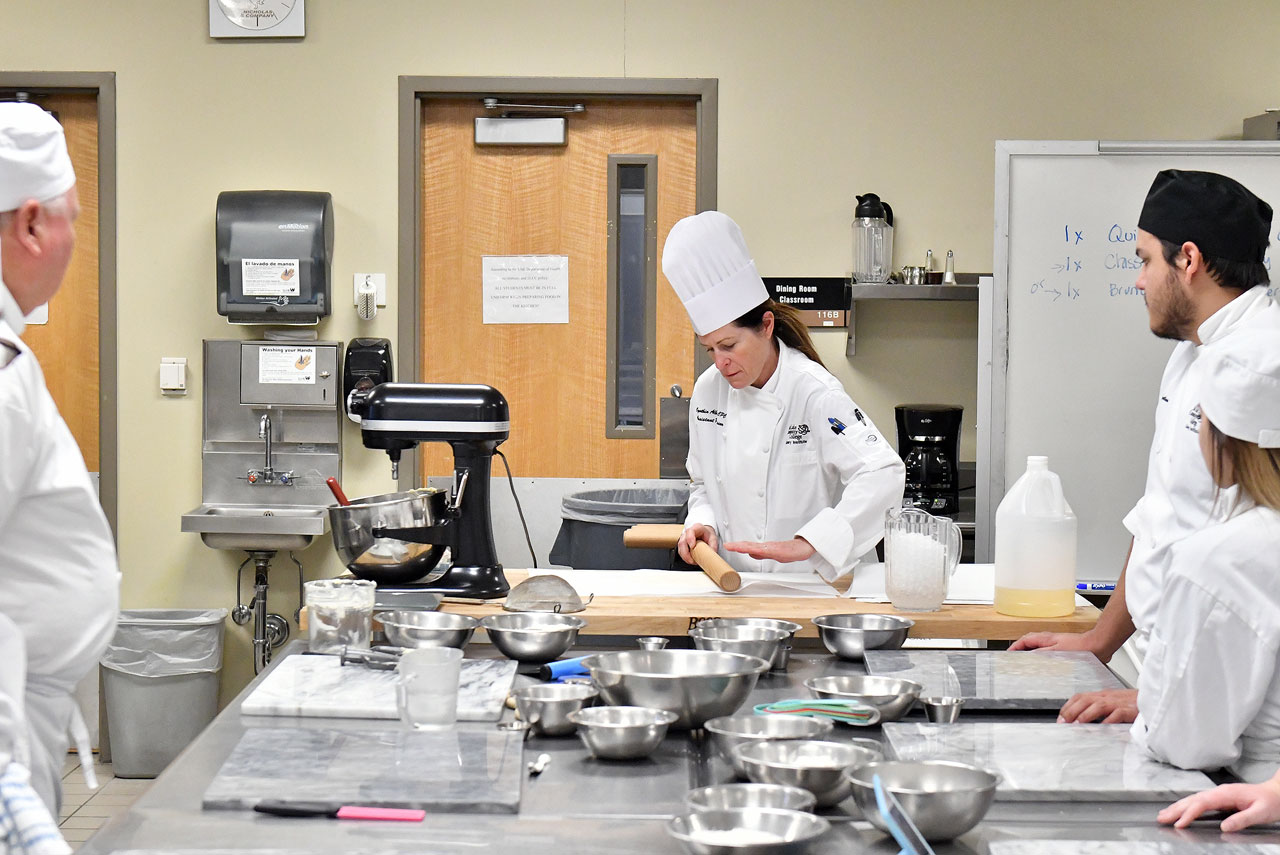 Cynthia Alberts instructs students in kitchen