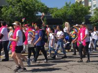 Parade marchers with rainbow fans and pink boas