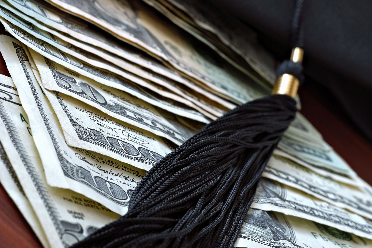 Higher education conceptual image with graduation cap and tassel on american currency
