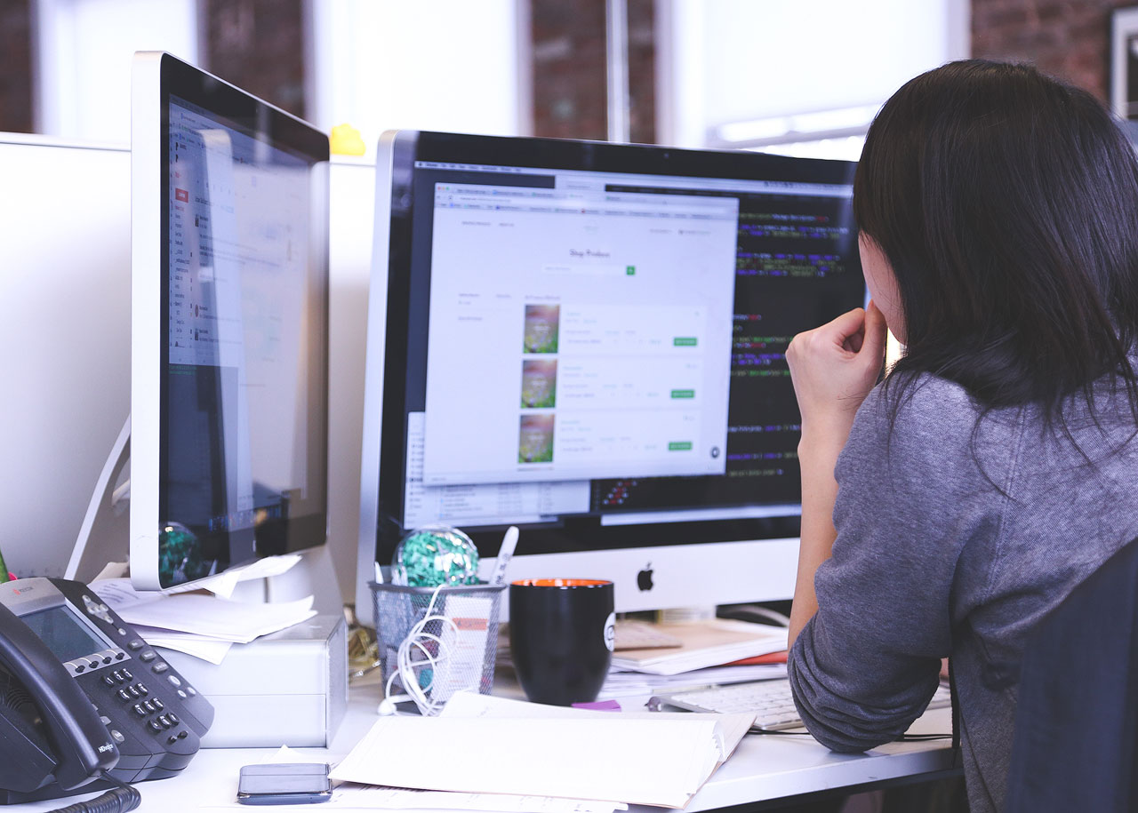 Woman viewing multiple computer screens at office workstation