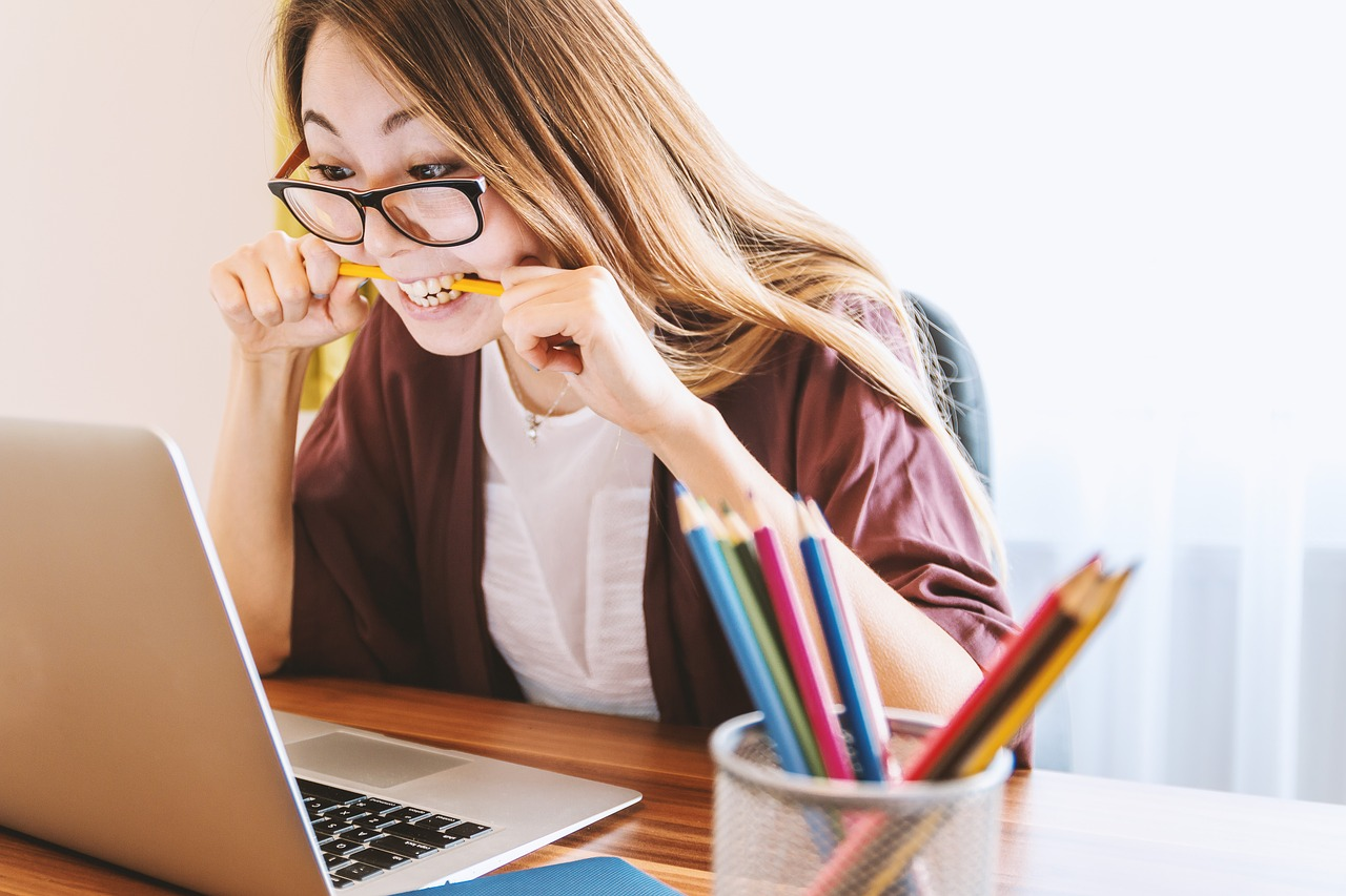 Woman biting pencil while using laptop