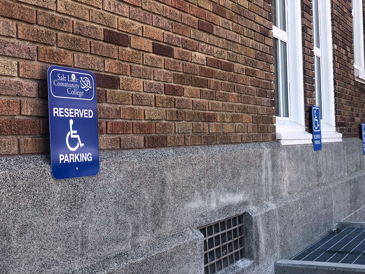 Disabled parking signs line wall of a building at South City Campus