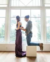 Leo Weffer kneels on stool behind female model