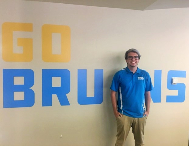 "Mason stands in front of ""Go Bruins"" mural"