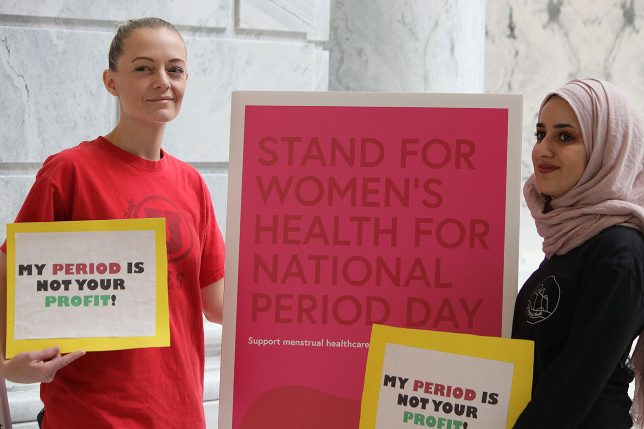 Two women stand with poster