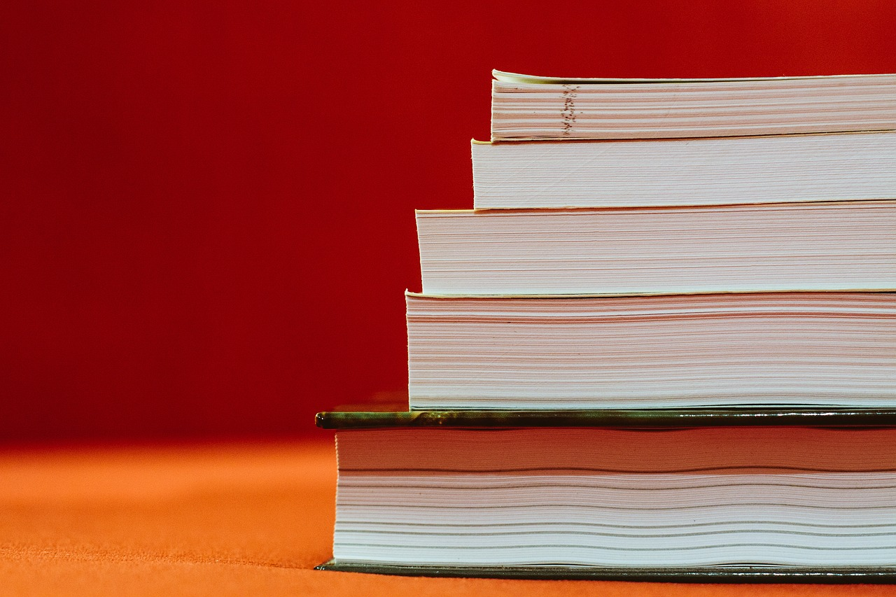 Stack of textbooks in front of red background