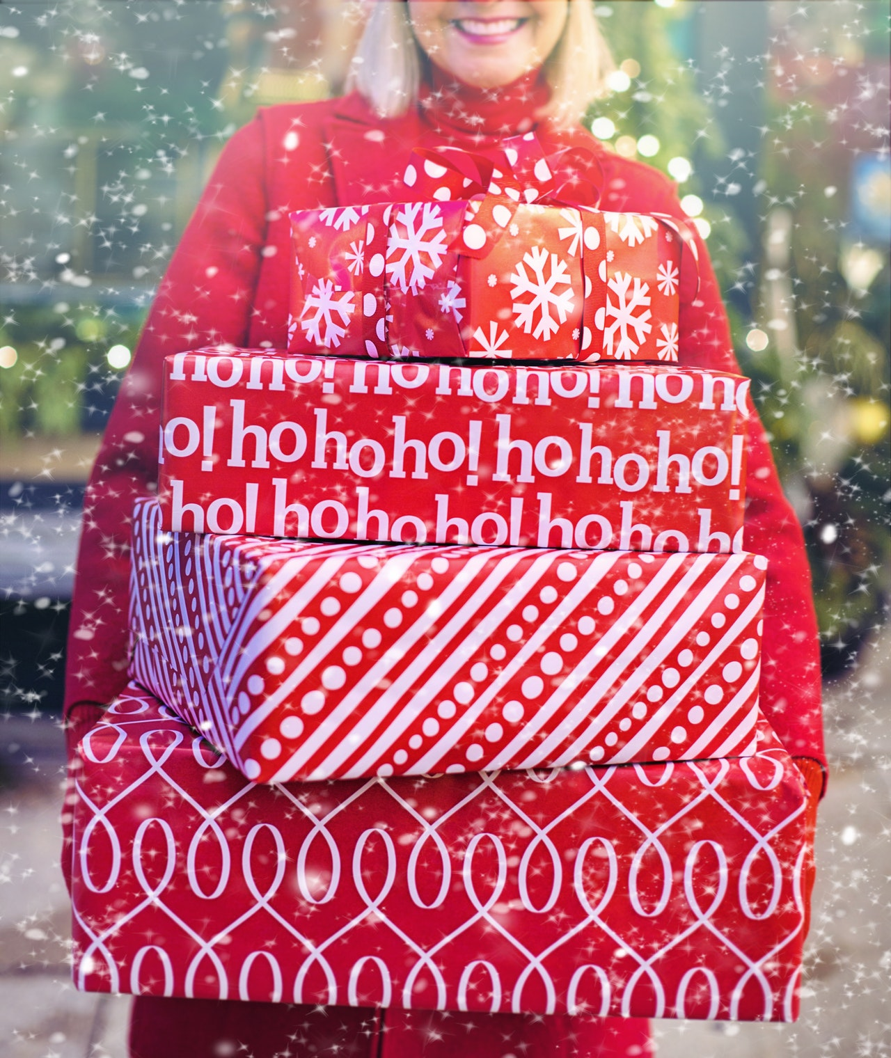 Woman carrying Christmas presents wrapped in red paper