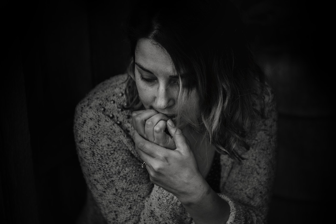 Grayscale photo of a woman biting her nails