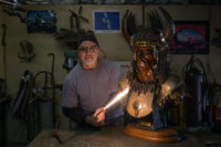 Richard holds a lit Oxy/Fuel torch next to metal sculpture of Four Bears