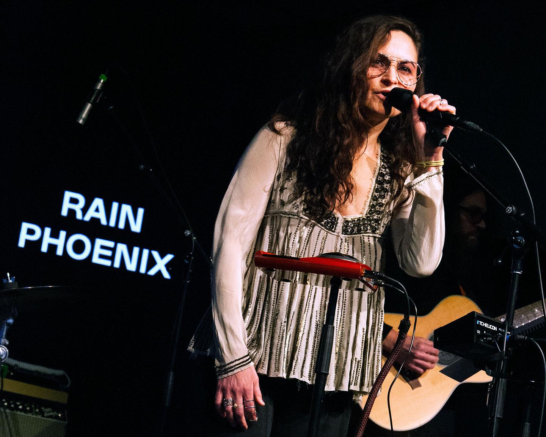 Rain Phoenix sings into the mic
