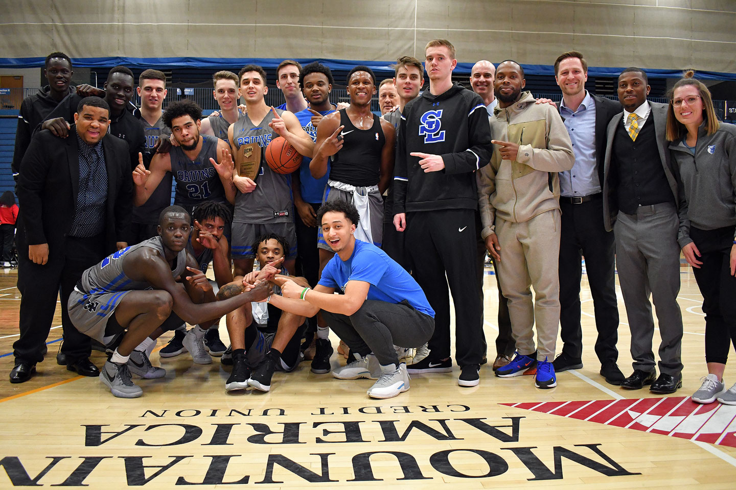 Men's basketball team with championship plaque