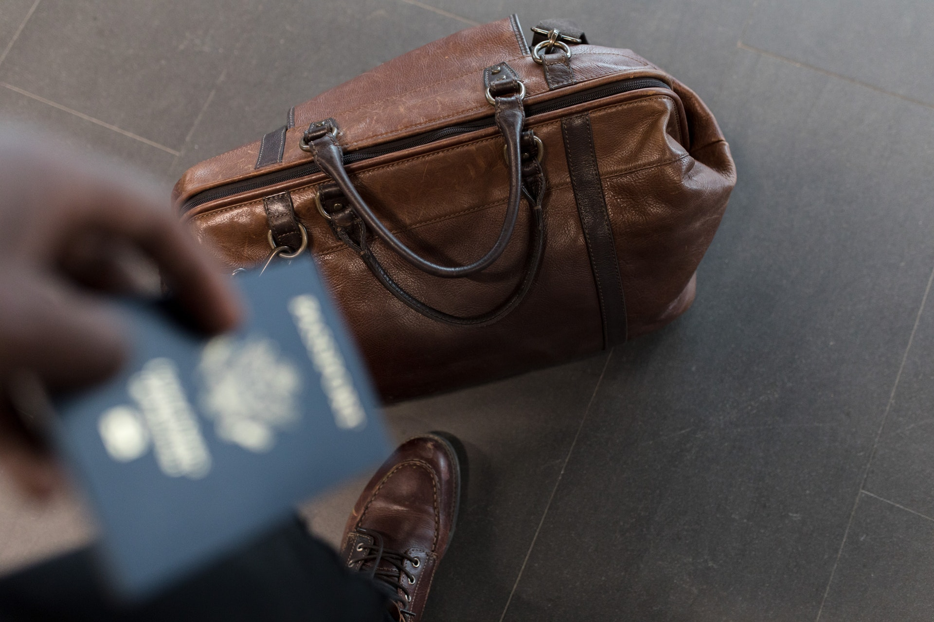 Traveler with passport and brown leather duffel bag in focus