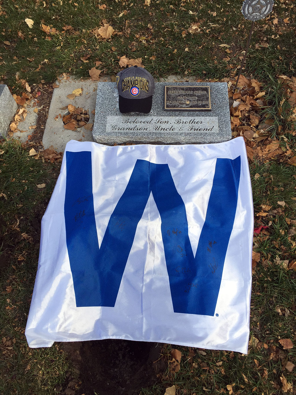Grave decorated with Chicago Cubs 'W' flag and hat