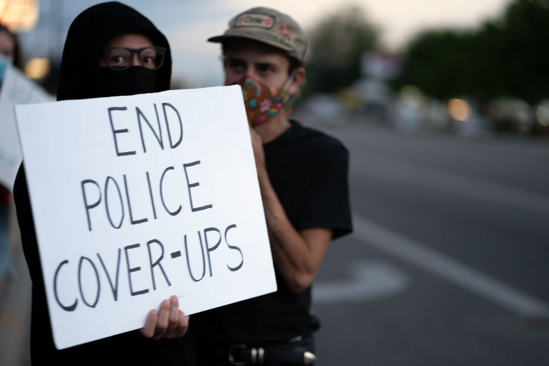 "Sign reads ""End police cover-ups"""