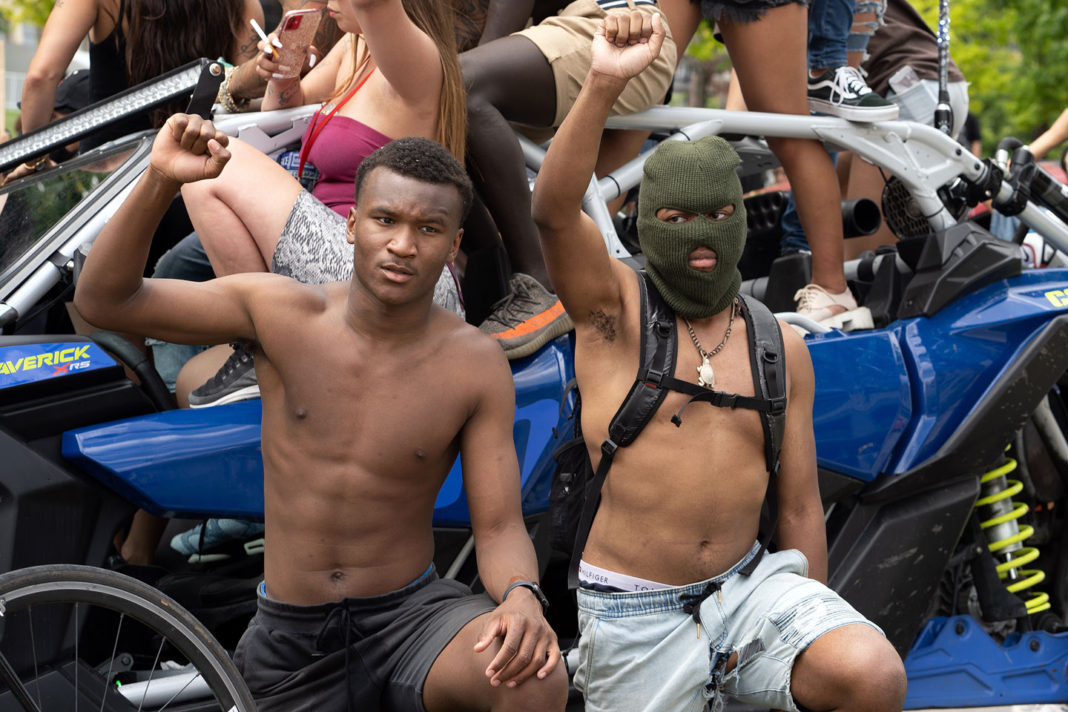 Two shirtless young men raise fists