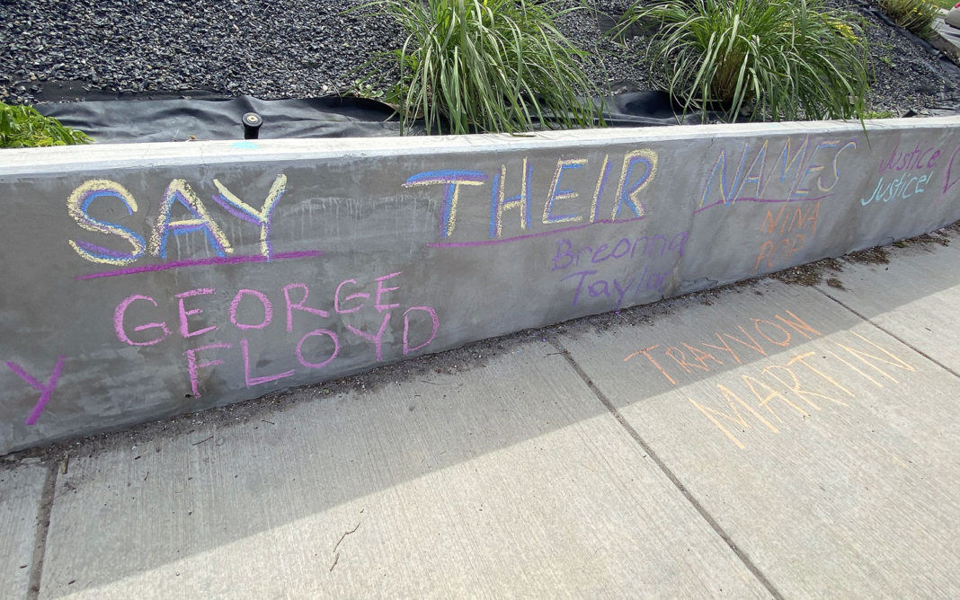"Chalk reads ""Say their names"""