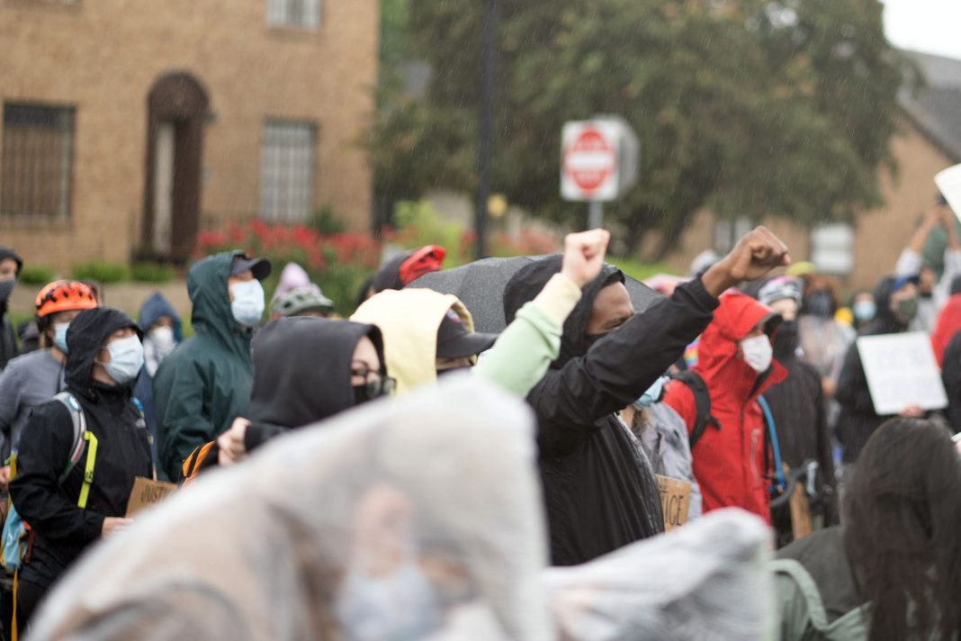 Protesters wearing masks and raising fists
