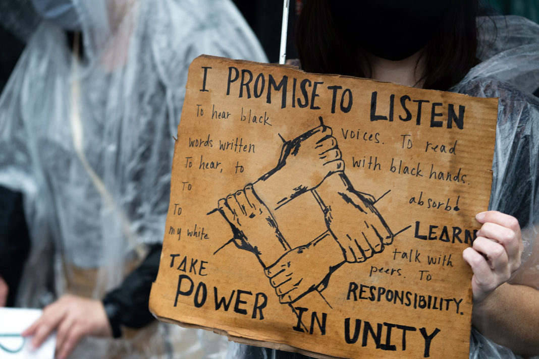"Sign reads ""I promise to listen. To hear black voices. To read words written with black hands. To hear, to absorb! To learn! To talk with my white peers. To take responsibility. Take power in unity"""