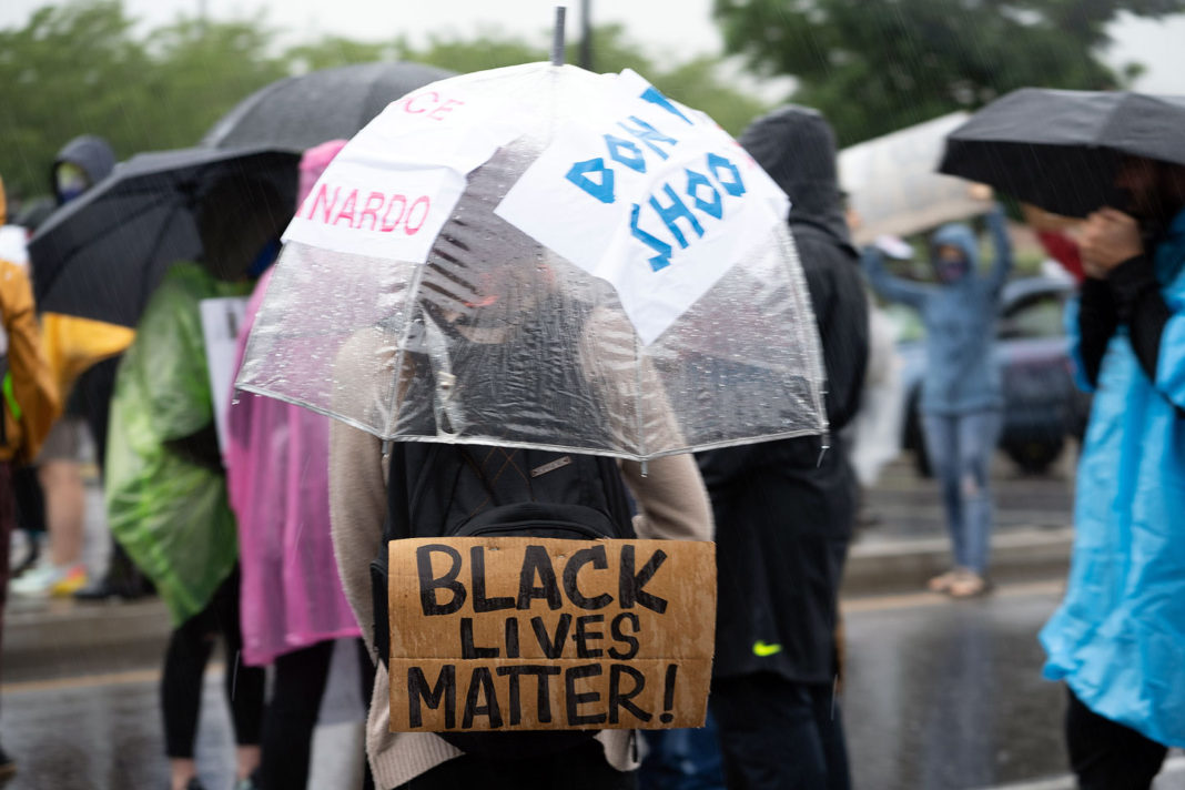 Rain-soaked protester carries several messages