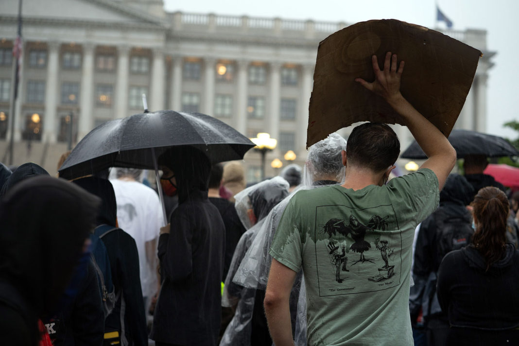Protester in t-shirt takes shelter under cardboard sign
