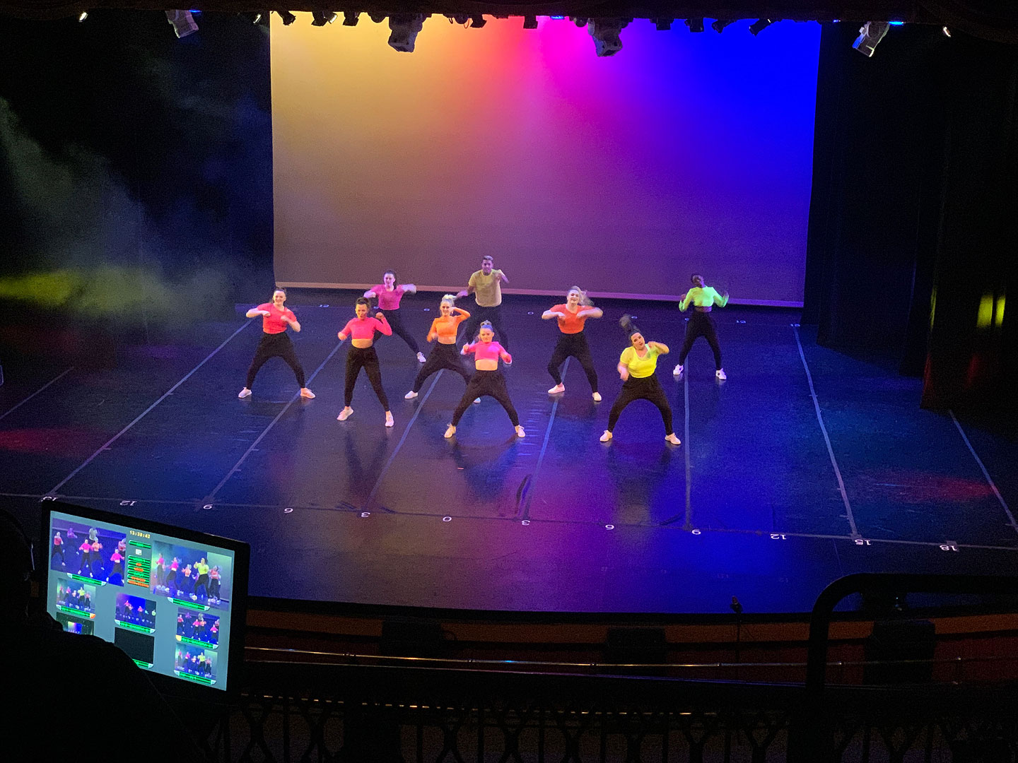 Nine dancers perform on stage