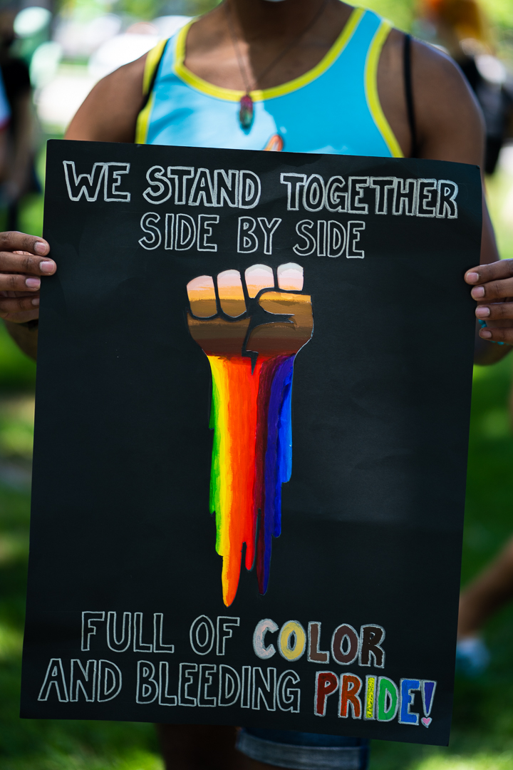 """Sign reads """"We stand together side by side, full of color and bleeding pride!"""""""
