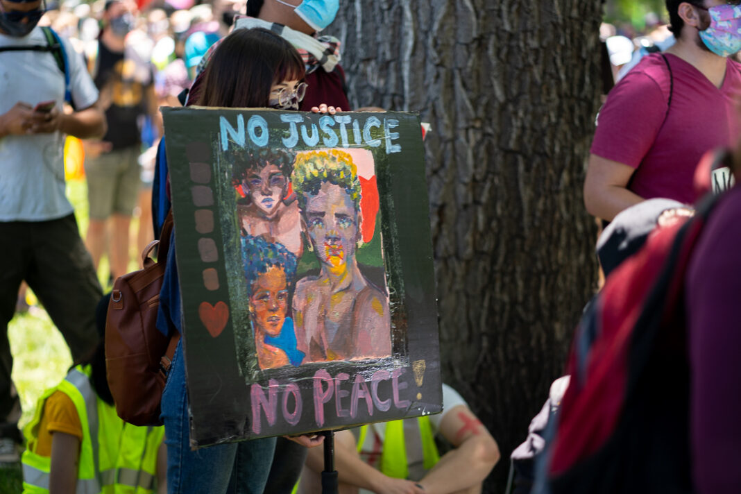 "Portraits painted on sign that reads ""No justice, no peace!"""
