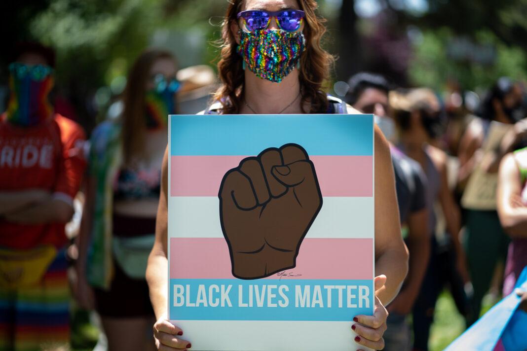 "Protester wearing mask holds sign that reads ""Black Lives Matter"""