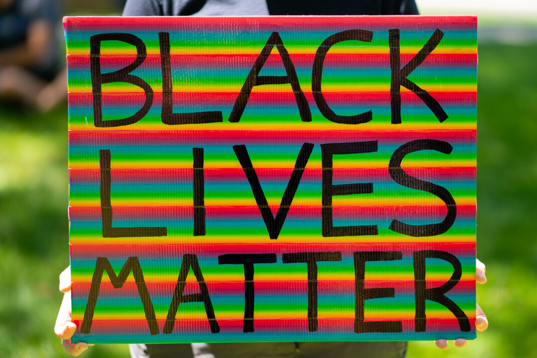 "Rainbow-colored sign reads ""Black Lives Matter"""