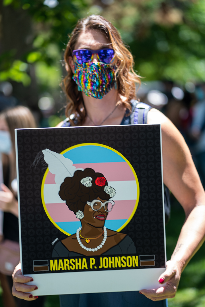 Masked demonstrator holds sign for Marsha P. Johnson