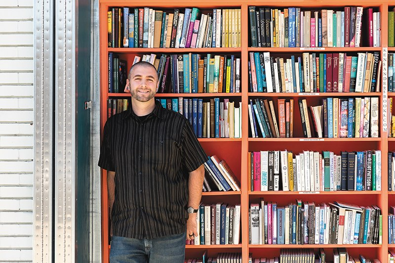 Michael stands in front of bookcase
