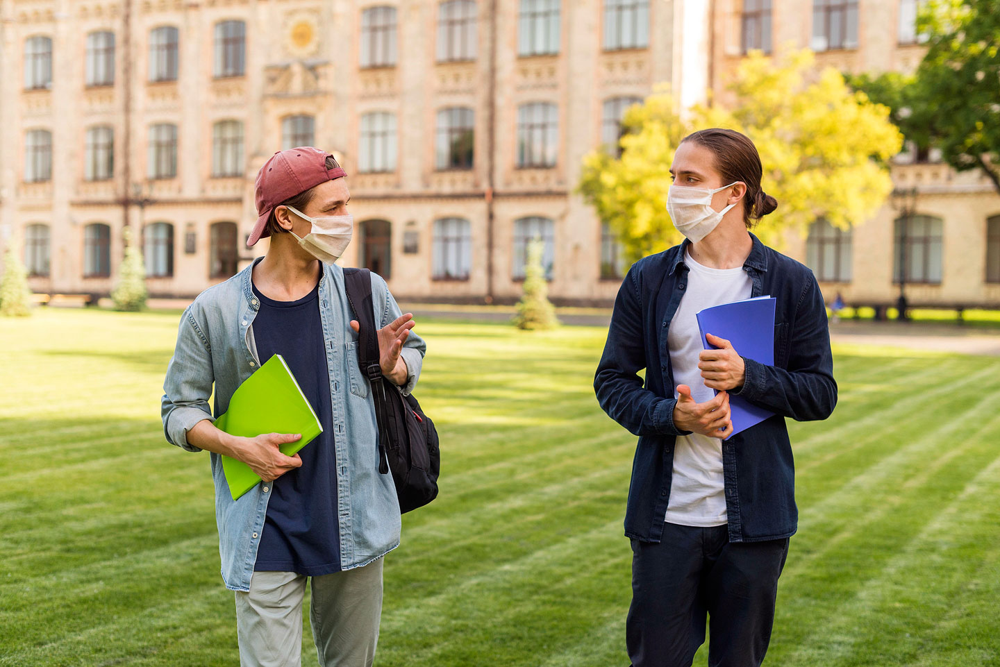 Male students socializing on campus while wearing masks