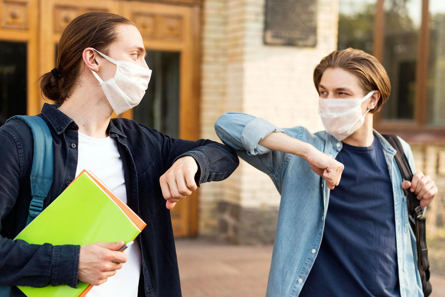 Young students bump elbows while wearing masks