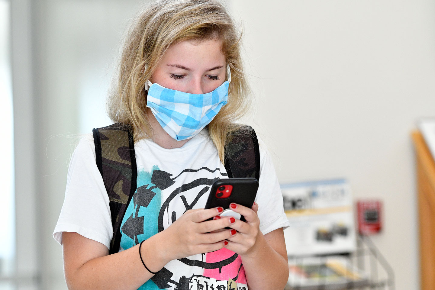 Student browses phone while wearing light blue mask
