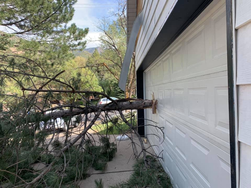 Wind strips siding off a house and puts tree through garage door