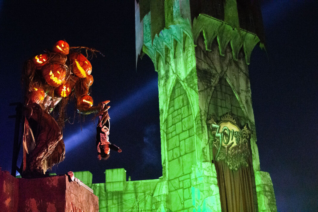 Pumpkin man holds ghoul beside green tower