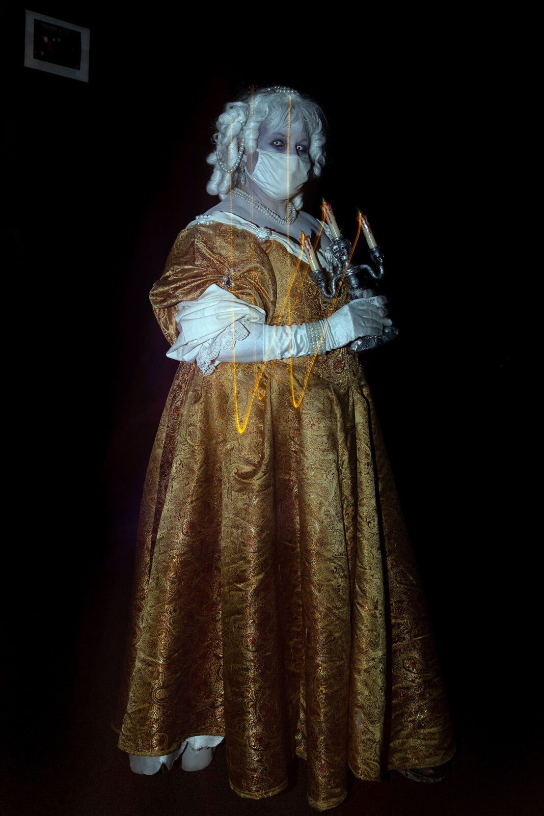 Lady Blanche, wearing a mask, holds a candle
