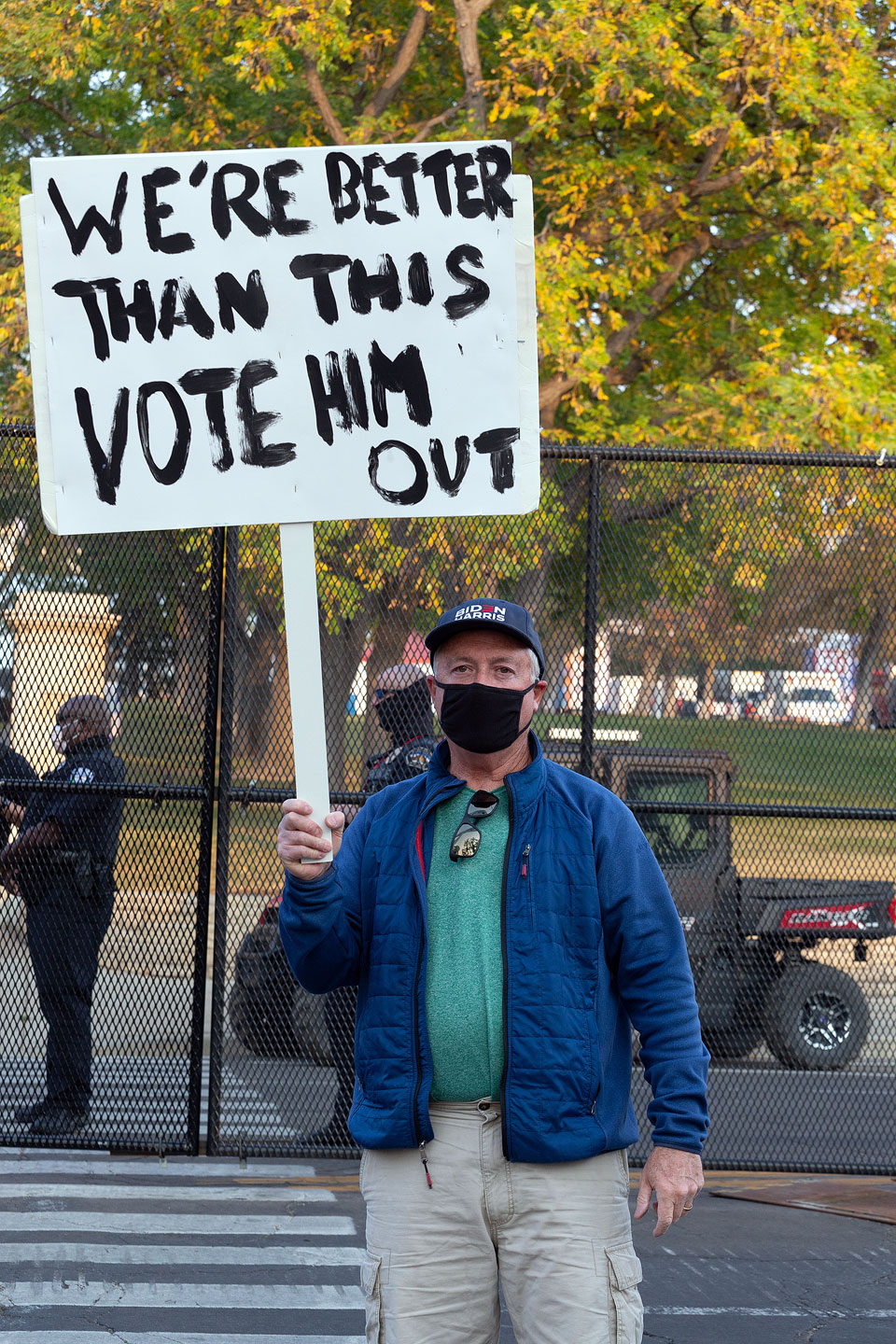 """Protester holds sign that reads """"We're better than this vote him out"""""""