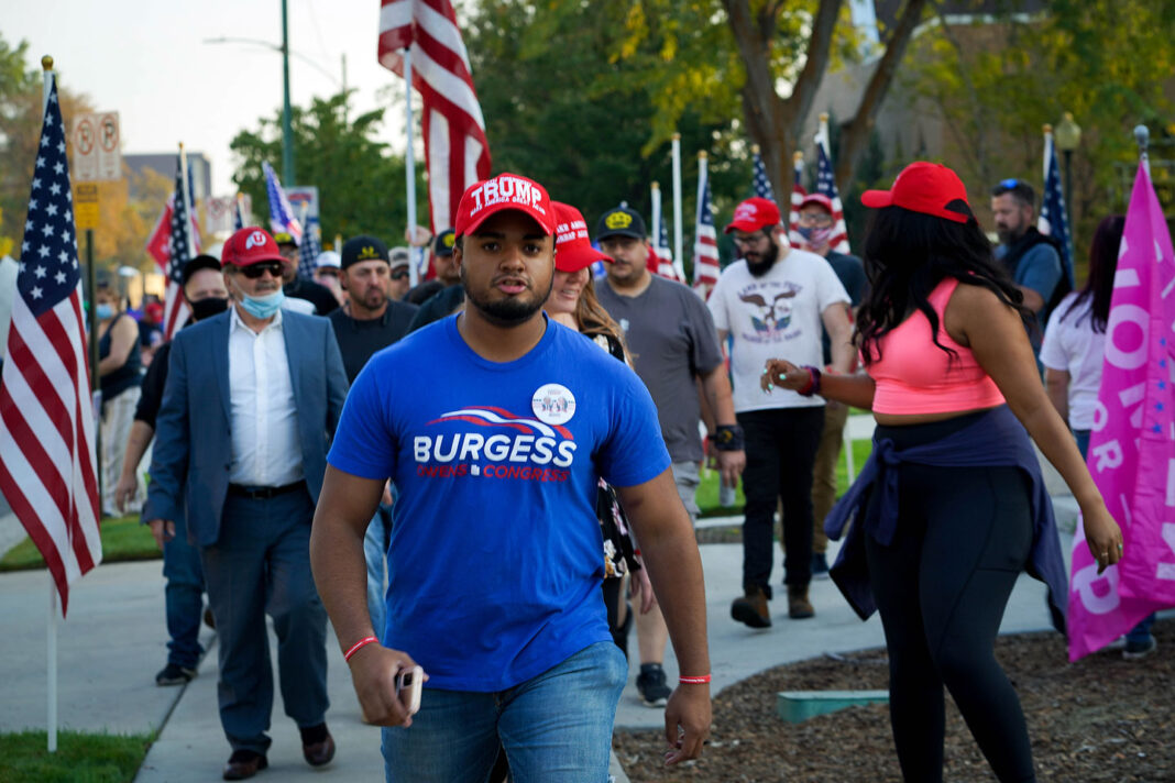 James wears blue Burgess Owens t-shirt and red MAGA hat